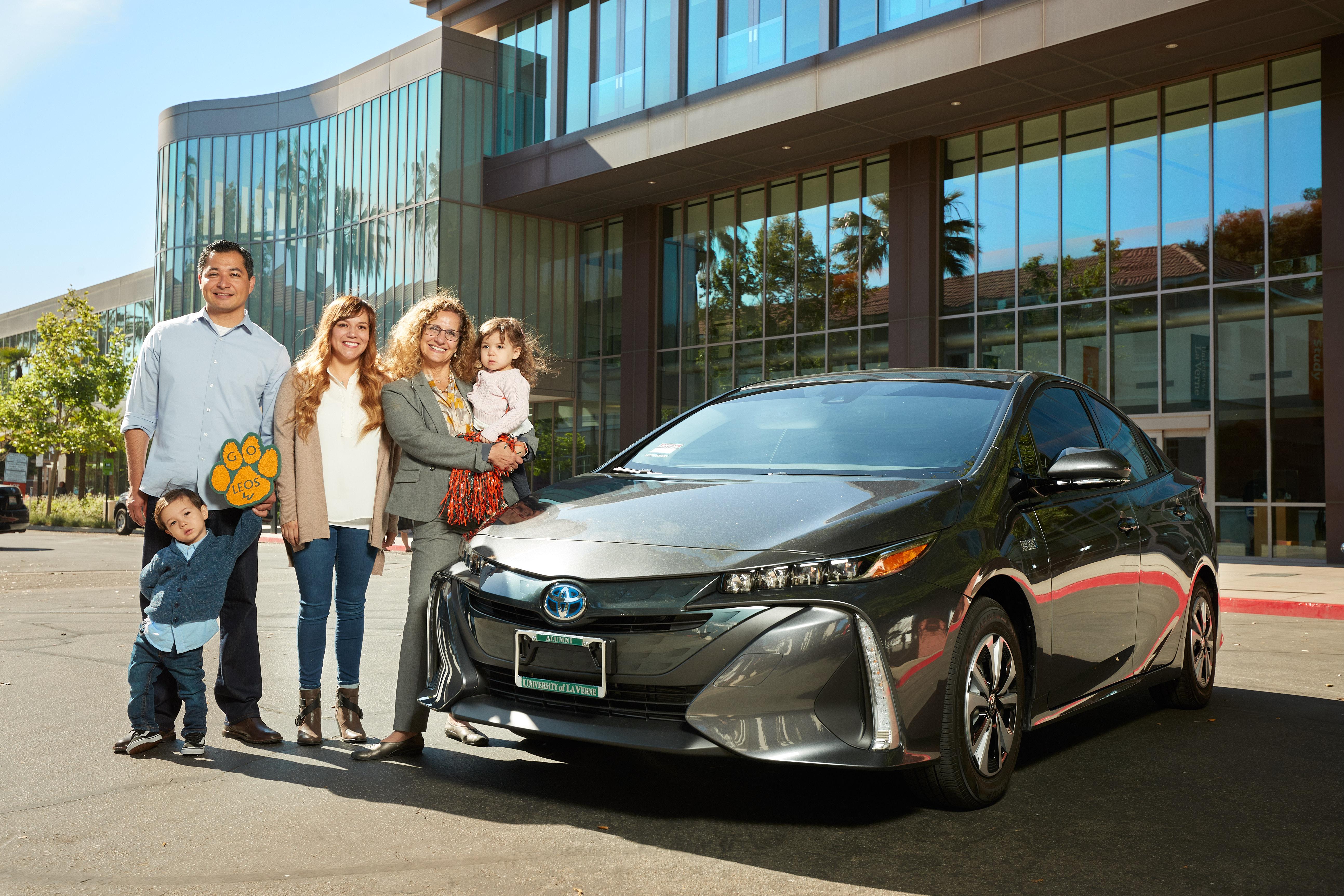 Scholarship fundraiser raffle winner poses with new Toyota Prius