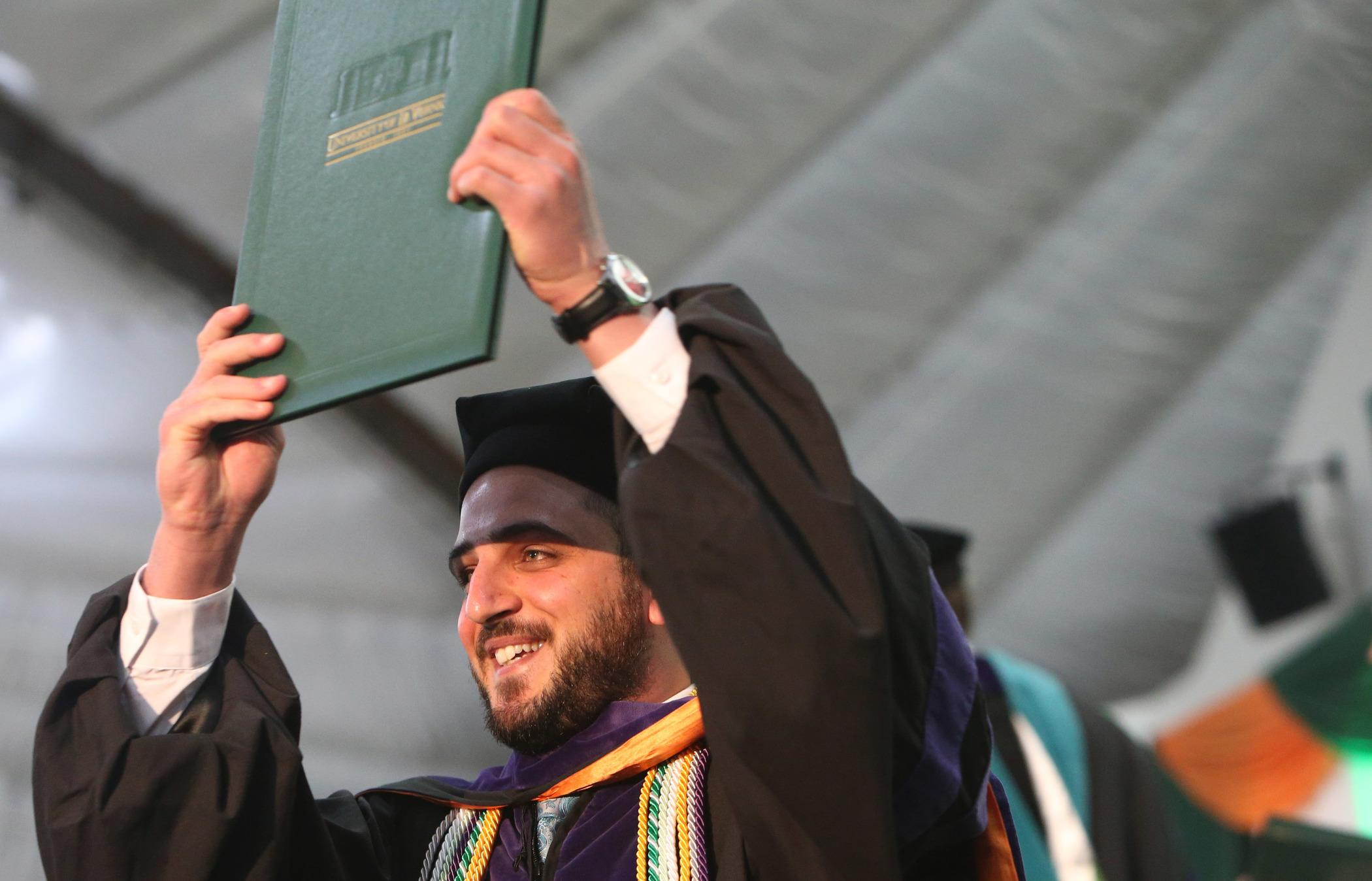 A College of Law graduate smiles onstage