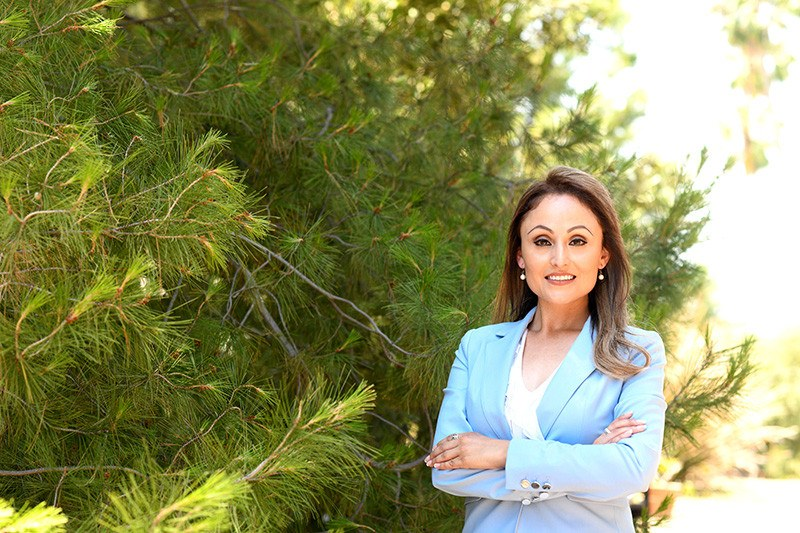 Female politician standing in front of trees