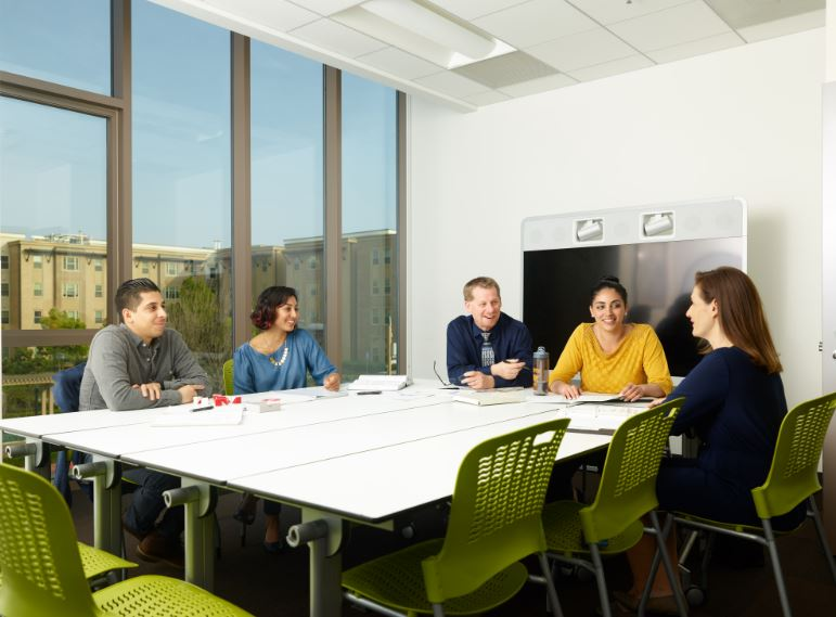 Professor and students gather around a table