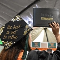A student shows off her decorated cap and diploma.