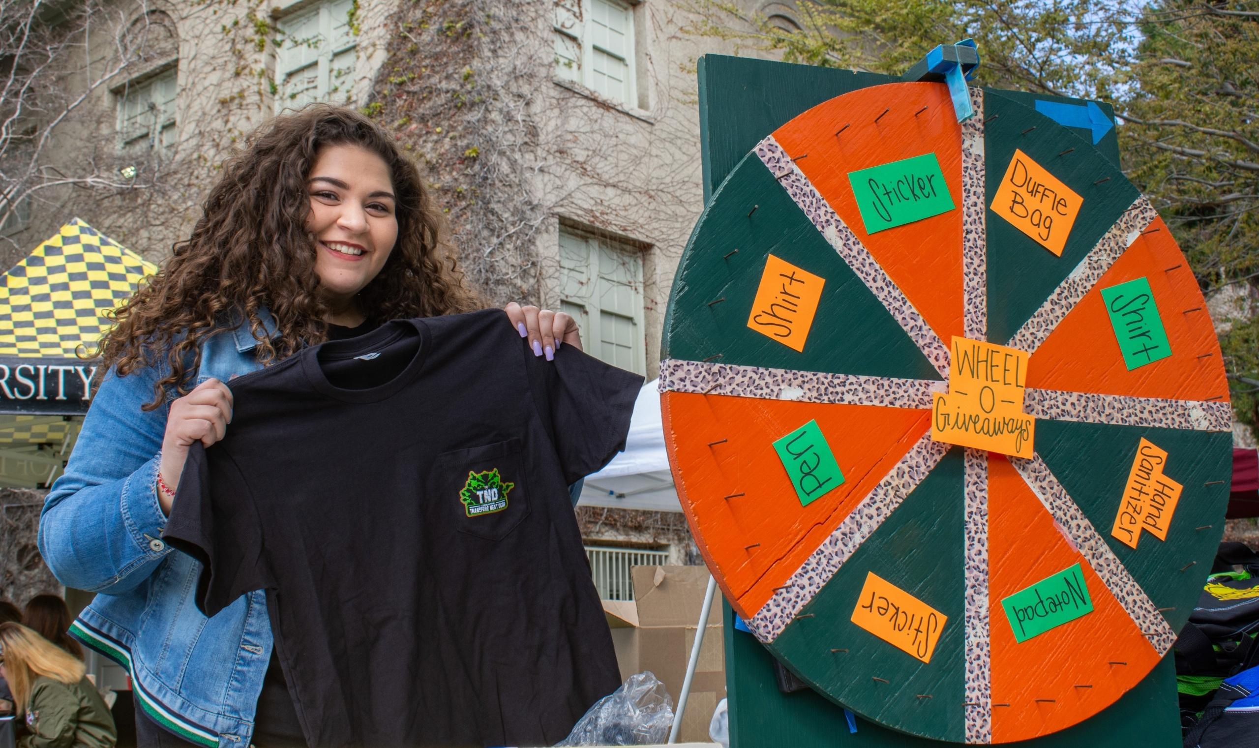 Transfer student holding a University of La Verne t-shirt