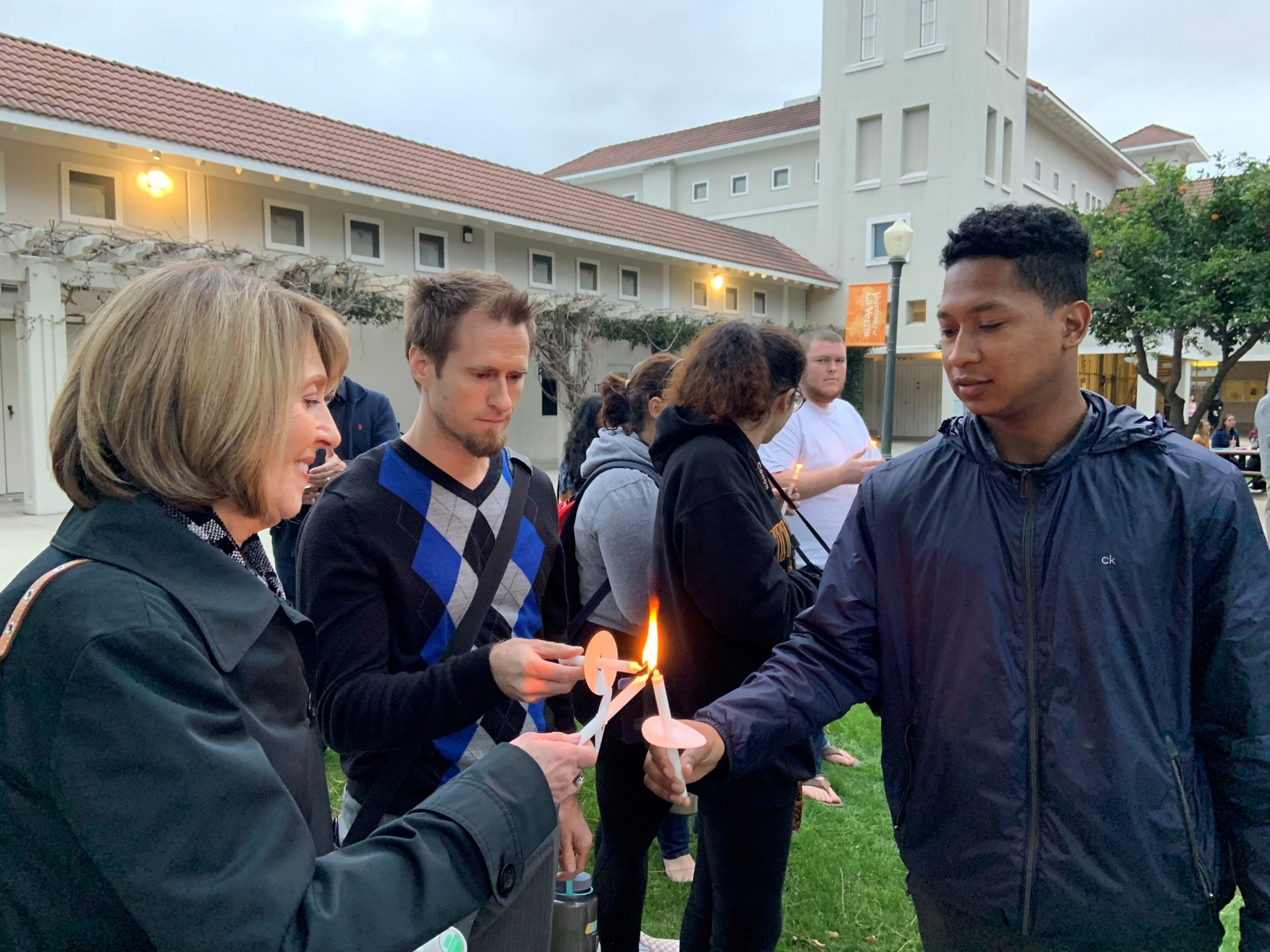 Students gather to light candles during vigil