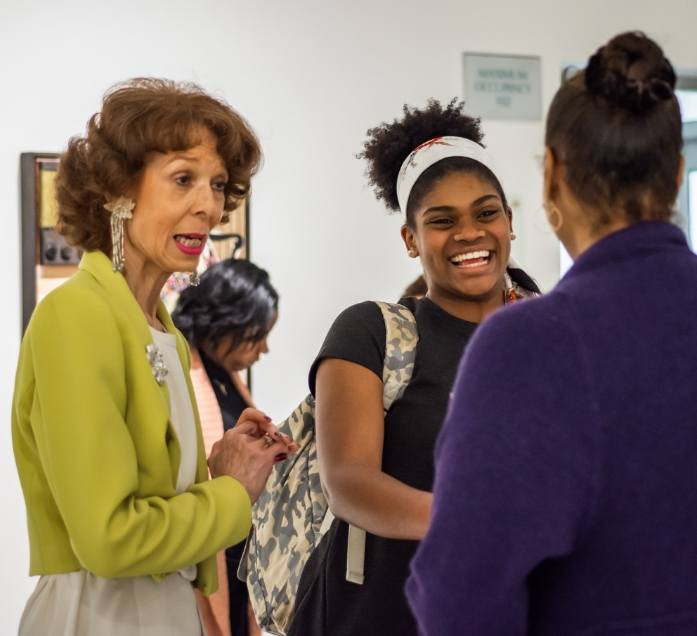 Artist Phoebe Beasley talks with attendees during reception.
