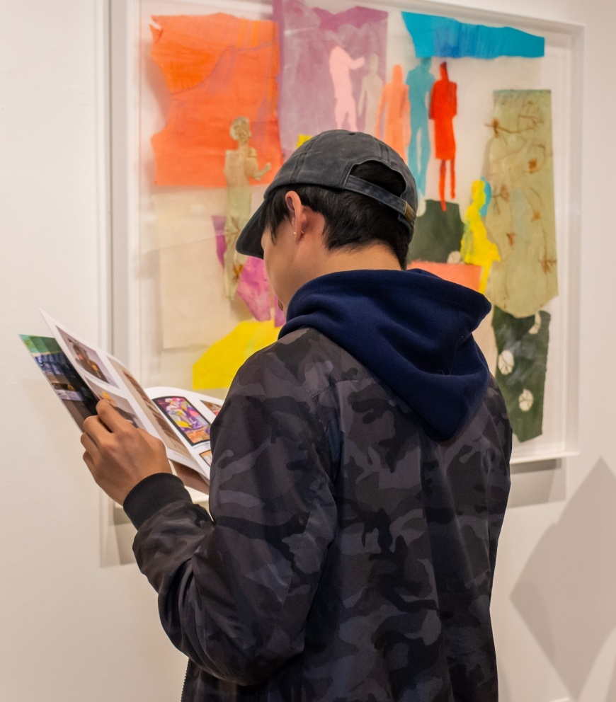 Student reads the artist's catalog