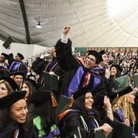 Students cheer at graduation.