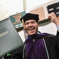 A male student celebrates with his degree.