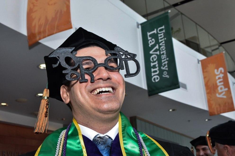 "A male student wears ""grad"" glasses."