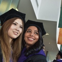 Female students smile in the Michael and Sara Abraham Campus Center after graduation.