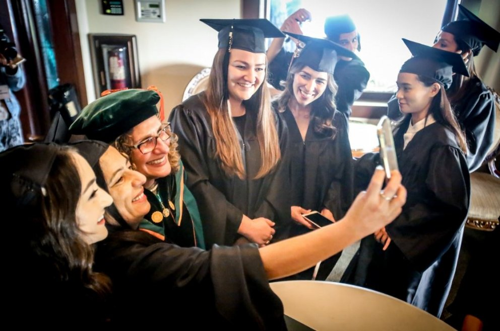 Students take photos with university president